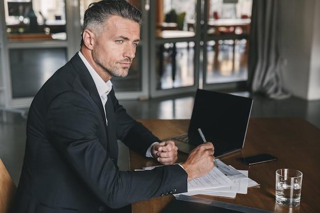 Afbeelding van geconcentreerde zelfverzekerde zakenman 30s dragen wit overhemd en zwart pak zittend aan tafel in kantoor, tijdens het werk met documenten en laptop