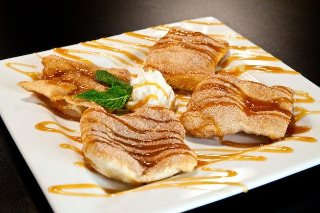 Afbeelding van gefrituurd deegdessert bestrooid met kaneelsuiker en besprenkeld met chocolade- en karamelsauzen op een witte plaat