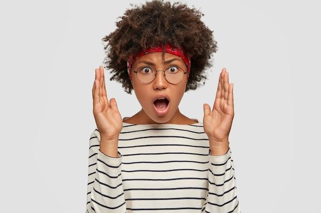 Afbeelding van geïrriteerde jonge vrouw met afro kapsel