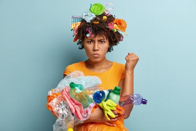 Afbeelding van geïrriteerde zwarte vrouw steekt gebalde vuist op, eist milieuvriendelijk te zijn, heeft knorrige gezichtsuitdrukking, draagt plastic afval, gebruikt voorwerpen voor recycling, staat over blauwe muur