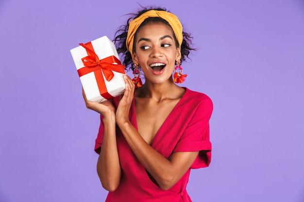 Afbeelding van gelukkig geïntrigeerde afrikaanse vrouw in jurk met geschenkdoos over paarse muur