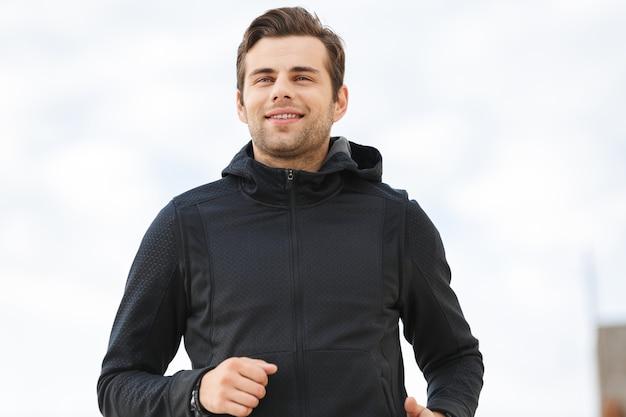 Afbeelding van gelukkig sportieve man 30s in zwarte sportkleding, loopt langs de pier aan zee