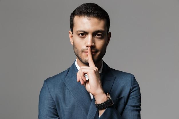 Afbeelding van gelukkige arabische zakenman 30s in formeel pak met wijsvinger op de lippen, geïsoleerd over grijze muur