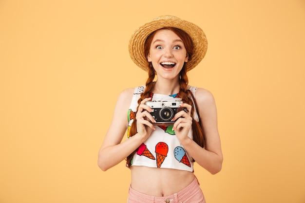 Afbeelding van gelukkige jonge mooie roodharige vrouw fotograaf toerist gekleed in ijs bedrukt t-shirt poseren geïsoleerd over gele muur met camera.