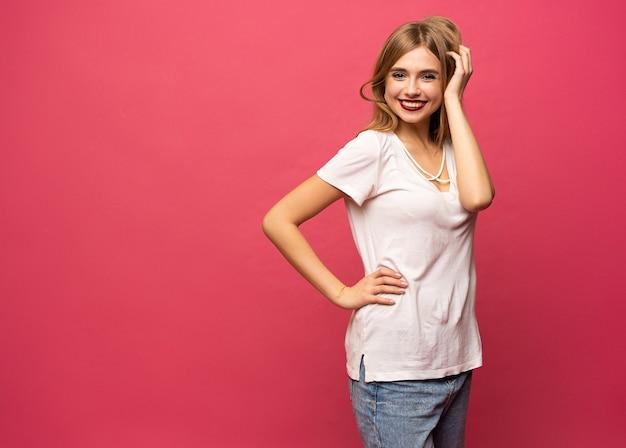 Afbeelding van gelukkige jonge vrouw geïsoleerd op roze achtergrond. kijkende camera wijst.