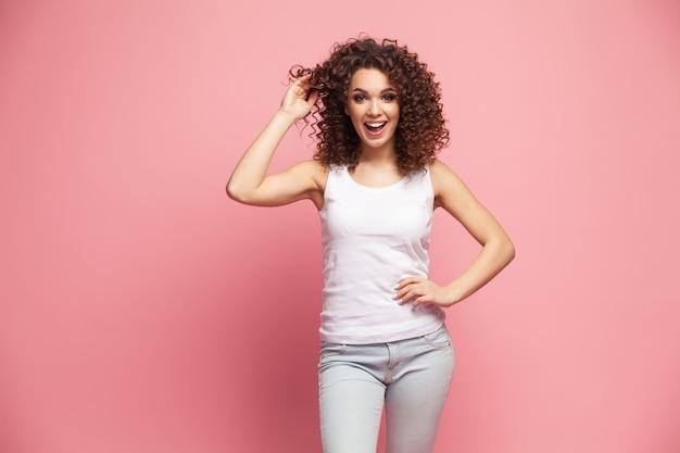 Afbeelding van gelukkige jonge vrouw geïsoleerd over roze