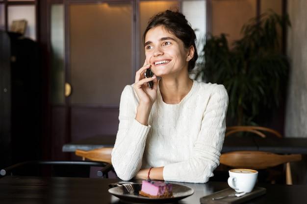 Afbeelding van gelukkige jonge vrouw zitten in café koffie drinken binnenshuis met behulp van mobiele telefoon praten.