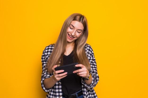 Afbeelding van gelukkige schattige mooie jonge vrouw spelletjes spelen via de mobiele telefoon geïsoleerd over gele muur muur. opzij kijken.