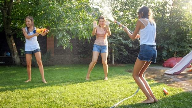 Afbeelding van gelukkige vrolijke kinderen met jonge moeder die speelt met waterpistolen en tuinhuis. familie spelen en plezier hebben buiten in de zomer