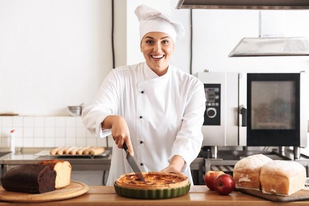 Afbeelding van gelukkige vrouw chef-kok dragen witte uniforme appeltaart houden, tijdens het koken in de keuken bij de bakkerij