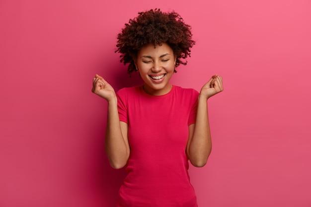 Afbeelding van gelukkige vrouw maakt vuist pomp gebaar, viert geweldig nieuws, giechelt positief, draagt vrijetijdskleding, lacht positief, vormt tegen felroze muur. emoties en succesconcept
