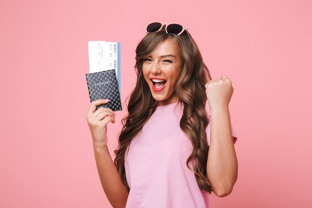 Afbeelding van gelukkige vrouw met mooie bruine sloten die haar vakantie verheugen terwijl ze paspoort en vliegtickets vasthoudt, geïsoleerd op roze achtergrond