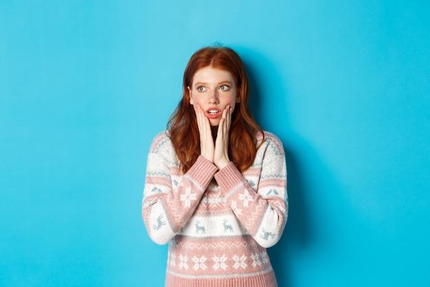 Afbeelding van geschokt en onder de indruk roodharig meisje realiseert iets, starend verbaasd, staande over blauwe achtergrond.