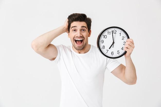 Afbeelding van geschokt opgewonden gelukkige jonge man poseren geïsoleerd over witte muur met klok.