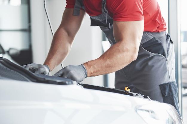 Afbeelding van gespierde autodienstmedewerker die voertuig repareert.