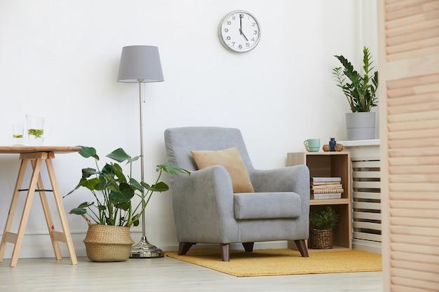 Afbeelding van gezellige fauteuil met ander modern meubilair in huiskamer
