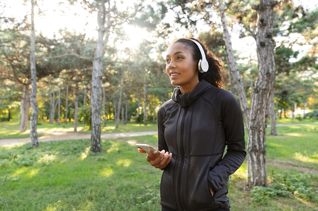 Afbeelding van gezonde vrouw 20s dragen zwarte trainingspak en koptelefoon, met behulp van mobiele telefoon tijdens het wandelen door groen park