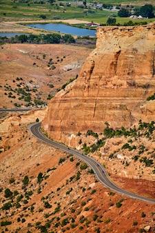 Afbeelding van gigantische rode rotskliffen in de kloof met weg en motorfietsen die er doorheen rijden