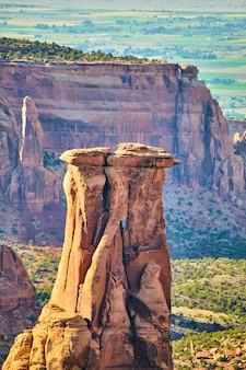 Afbeelding van gigantische rotspilaar in het midden van de kloof omringd door kliffen