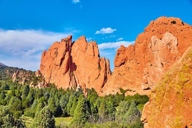 Afbeelding van gigantische uitstulpingen van rode rotsen in bergen en groen bos