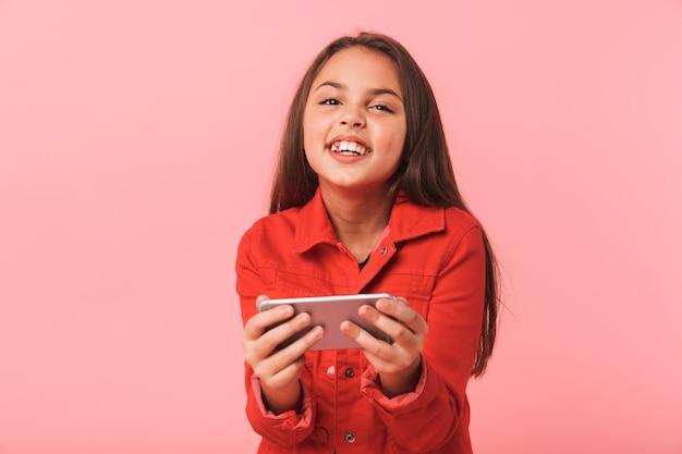 Afbeelding van glimlachend tienermeisje in casual spelen van videogames op mobiele telefoon terwijl staande, geïsoleerd over rode muur