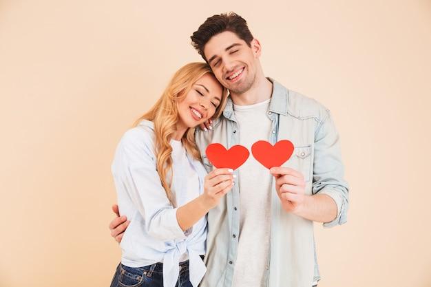 Afbeelding van glimlachende man en vrouw verliefd die denim kleding dragen die samen met gesloten ogen knuffelen en twee rode papieren harten vasthouden, geïsoleerd over beige muur