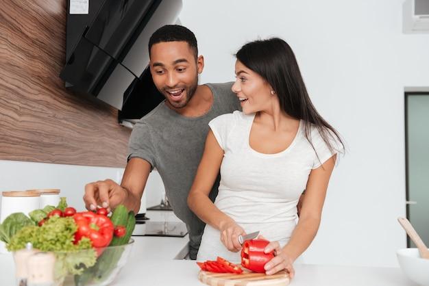 Afbeelding van grappig jong koppel in de keuken koken. de mens neemt de producten weg.