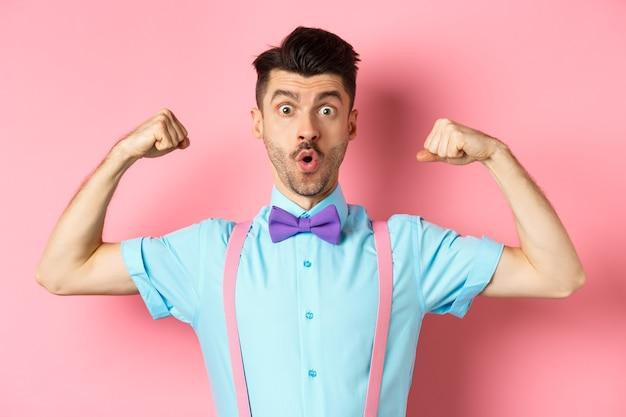 Afbeelding van grappige kerel met snor en 'bow-tie, spieren tonen, biceps buigen en verbaasd kijken naar camera, staande in ongeloof op roze achtergrond.