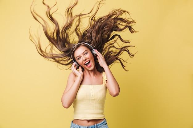 Afbeelding van grappige vrouw 20s zingen en plezier maken met haar schudden tijdens het luisteren naar muziek via koptelefoon, geïsoleerd op gele achtergrond