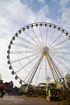 Afbeelding van groot reuzenrad in het midden van een kermis tegen een gedeeltelijk bewolkte hemel