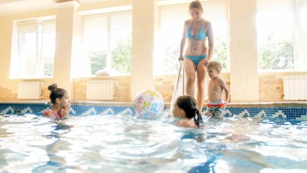 Afbeelding van grote familie die in het binnenzwembad van het huis zwemt