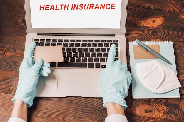 Afbeelding van handen in medische handschoenen op de achtergrond van een laptop. de vrouw houdt een plastic bankpasje vast en typt het nummer in op de website. online winkelconcept. beveiliging tijdens quarantaine