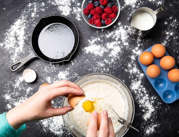 Afbeelding van handen van man eieren breken in kom. tafel met bessen, melk, bloem. foto van bovenaf