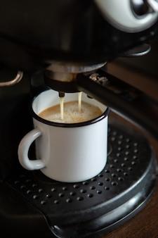 Afbeelding van het gieten van koffie uit koffiemachine in mok in de keuken