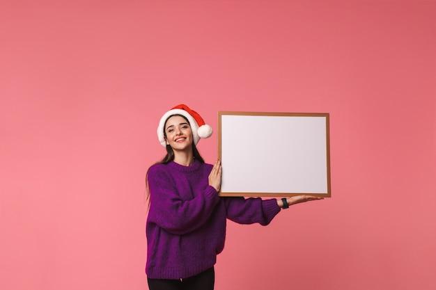 Afbeelding van het mooie gelukkige jonge emotionele vrouw stellen geïsoleerd over roze holdings copyspace leeg.