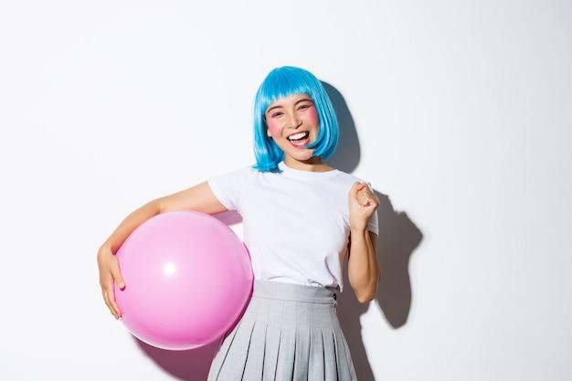 Afbeelding van het winnen van een vrolijk aziatisch meisje, dat er gelukkig en triomfantelijk uitziet, vakantie viert, feestkleding en een blauwe pruik draagt