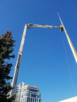 Afbeelding van hoge mobiele kraan met manipulator en emmer voor arbeiders tegen blauwe lucht en felle zon