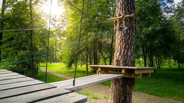 Afbeelding van houten brug en touwen die tussen de bomen in het park hangen. extreem avonturenpark voor entertainment voor kinderen en volwassenen