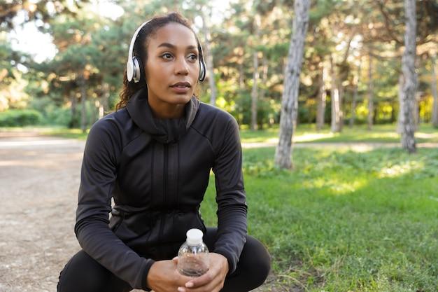Afbeelding van jonge amerikaanse vrouw 20s dragen zwarte trainingspak en koptelefoon, waterfles vasthouden tijdens het wandelen door groen park
