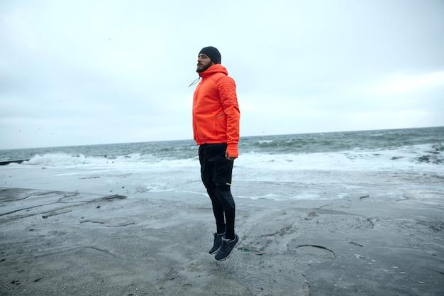 Afbeelding van jonge atletische bebaarde man in zwarte sportieve kleding en warme oranje jas met capuchon springen met gevouwen handen langs zijn lichaam om op te warmen, geïsoleerd over zeezicht