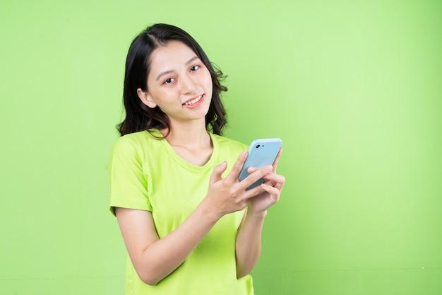 Afbeelding van jonge aziatische vrouw met smartphone op groene achtergrond