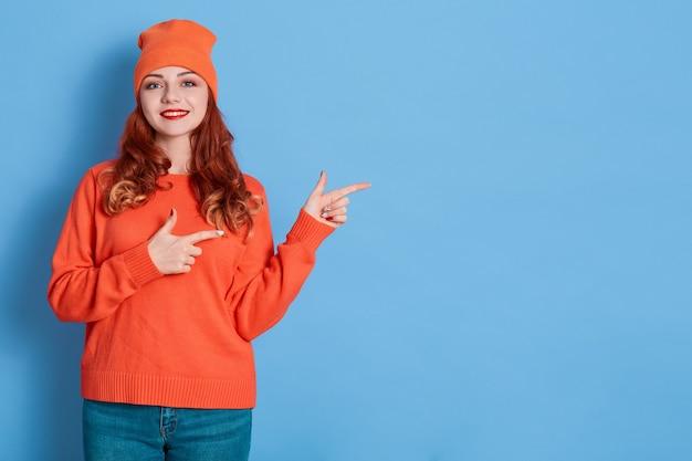 Afbeelding van jonge gelukkige vrouw staat glimlachend en wijzende vingers opzij op kopie ruimte geïsoleerd