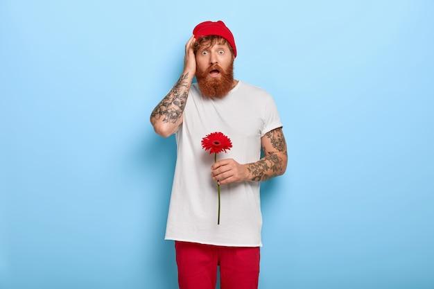Afbeelding van jonge hipster houdt rode gerberabloem vast, komt op datum, geschokt om vriendin met andere man op te merken