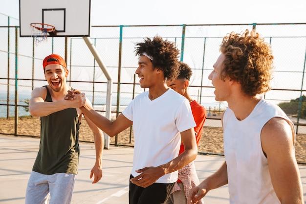 Afbeelding van jonge mannen basketballers staan op de speelplaats buiten, tijdens zonnige zomerdag