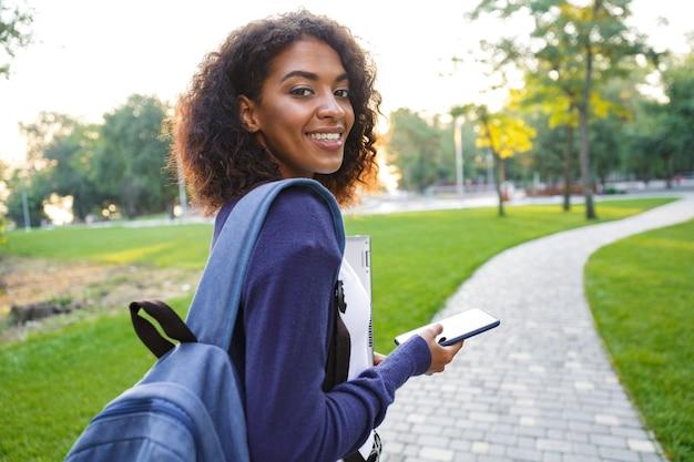 Afbeelding van jonge mooie afrikaanse vrouw student wandelen in het park chatten via de mobiele telefoon.