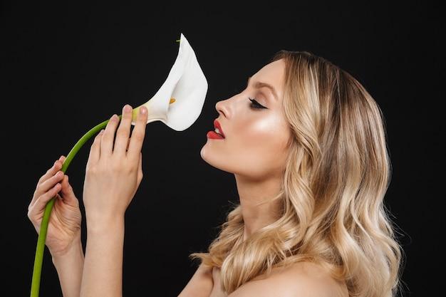 Afbeelding van jonge mooie vrouw met lichte make-up rode lippen poseren geïsoleerde bedrijf bloem.