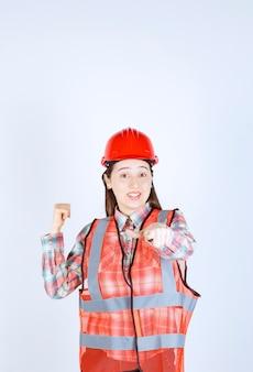 Afbeelding van jonge mooie vrouwelijke ingenieur in helm die ergens naar wijst.