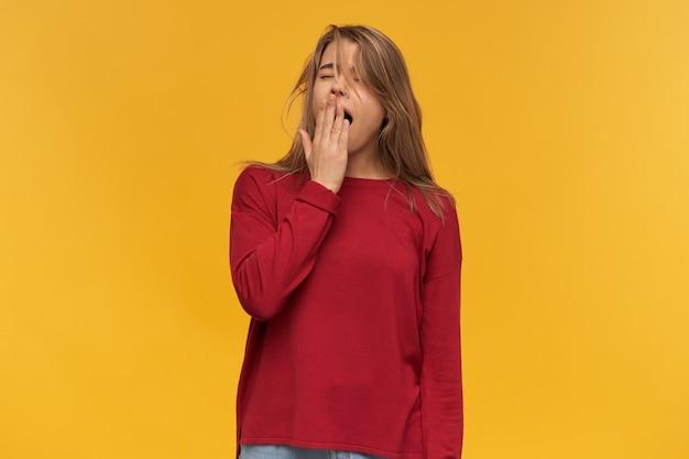 Afbeelding van jonge student, draagt rode trui en spijkerbroek, geeuw met gesloten ogen