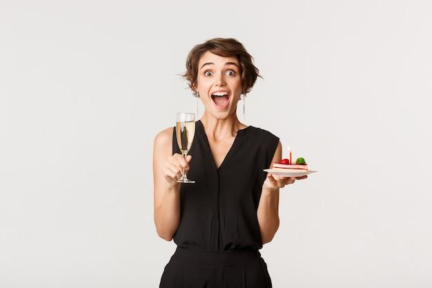Afbeelding van jonge verbaasde vrouw wonen verjaardagsfeestje, met glas champagne en cake.