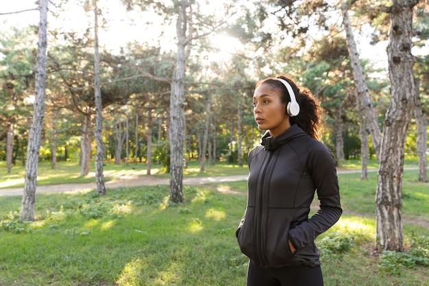 Afbeelding van jonge vrouw 20s dragen zwarte trainingspak en koptelefoon, wandelen door groen park